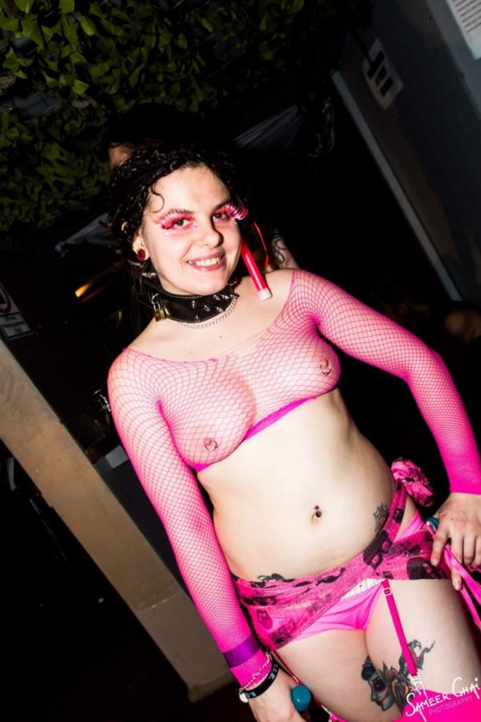 Bambi Biohazard in alternative makeup, pink fishnet top and pink stockings.